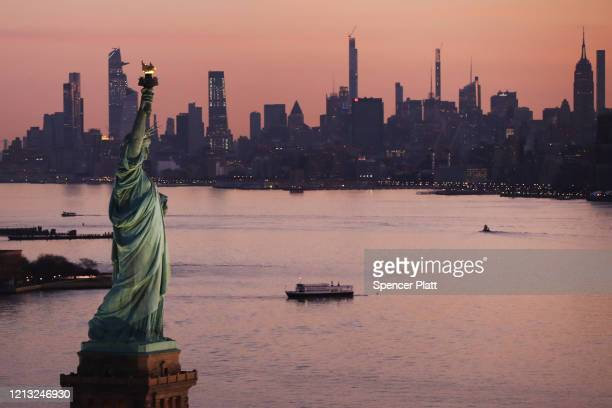 Dawn breaks over The Statue of Liberty as Manhattan and the nation struggles to contain the number of coronavirus cases on March 18, 2020 in New York...