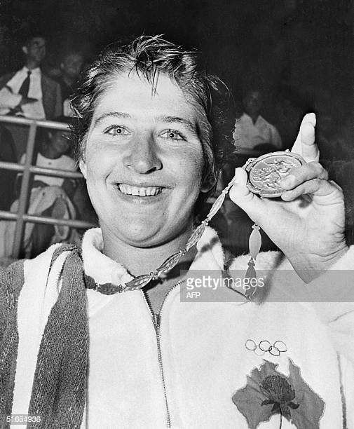 Dawn Fraser from Australia shows her gold medal that she won at the 100meter freestyle swimming 30 August 1960 during the Olympic Games held in Rome