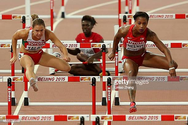 Dawn Harper Nelson of the United States falls as Alina Talay of Belarus and Sharika Nelvis of the United States continue down the track during the...