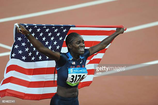 Dawn Harper of the US holds her national flag as she celebrates winning the women's 100m Hurdles final at the National Stadium during the 2008...