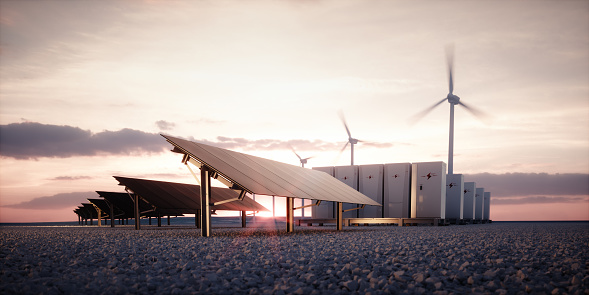 Dawn of new renewable energy technologies. Modern, aesthetic and efficient dark solar panel panels, a modular battery energy storage system and a wind turbine system in warm light. 3D rendering. 1128888172