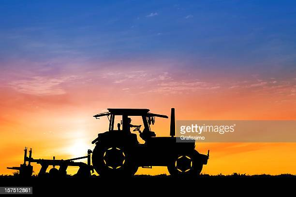 Dawn over tractor plowing a field