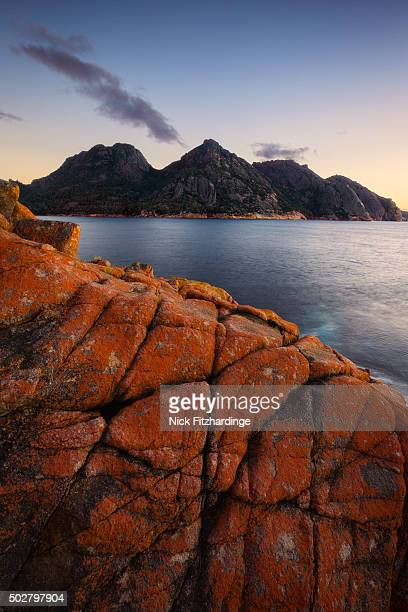 Dawn over Wineglas Bay and a section of rock covered in red lichen with the Hazards mountain range behind, Freycinet National Park, Tasmania, Australia