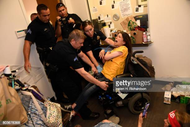 Dawn Russell gets arrested by Denver police officers after refusing the vacate the offices of Senator Cory Gardner on June 29 2017 in Denver Colorado...