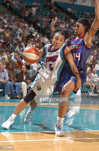 Dawn Staley of the Charlotte Sting drives around Deanna Nolan of the Detroit Shock during the game on July 27 2002 at Charlotte Coliseum in Charlotte...