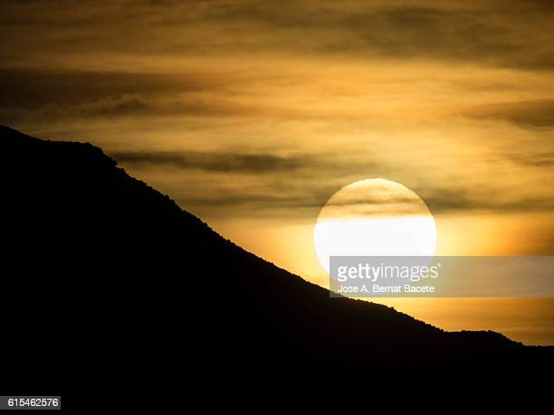 Dawn, sunrise behind a mountain with clouds yellow and orange. Spain