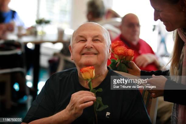 Dawn Vaillancourt left gave Bill Flesher a flower during a birthday celebration for residents of Walker Methodist Westwood Ridge community members...
