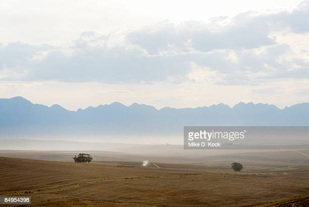 a dawn view of rolling fields in the overberg with the riviersonderend mountains in the background, overberg, western cape province, south africa - overberg stock pictures, royalty-free photos & images