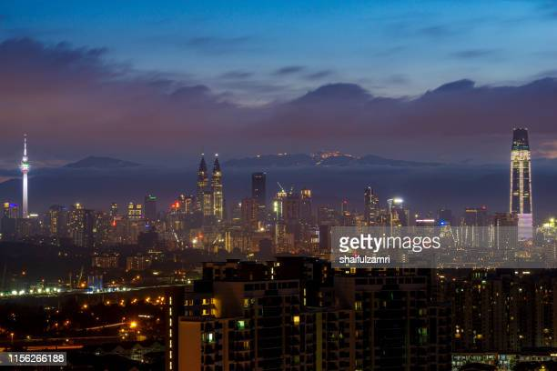dawn view over downtown kuala lumpur with genting highlands seen as background. - shaifulzamri stockfoto's en -beelden