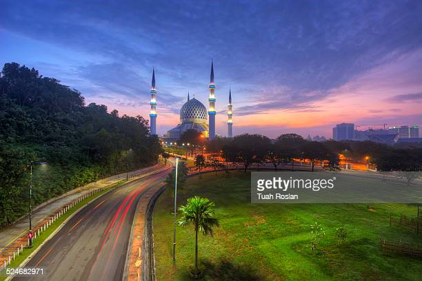 Dawn with mosque and light trail