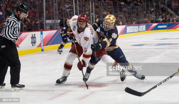 Dawson Cook of the Notre Dame Fighting Irish checks Henrik Borgstrom of the Denver Pioneers during game two of the 2017 NCAA Division I Men's Hockey...
