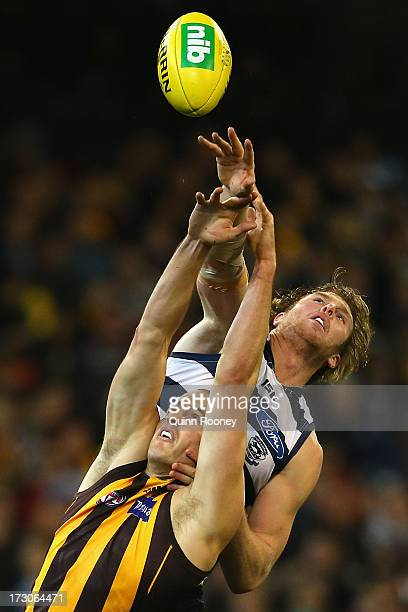 Dawson Simpson of the Cats taps the ball out of the ruck against David Hale of the Hawks during the round 15 AFL match between the Geelong Cats and...