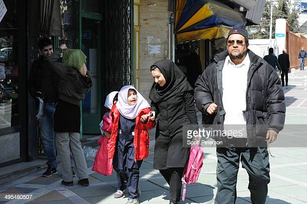 Dawud Salahuddin, an African-American convert to Islam who was born David Theodore Belfield , walks along ValiAsr Street next to a woman and two...