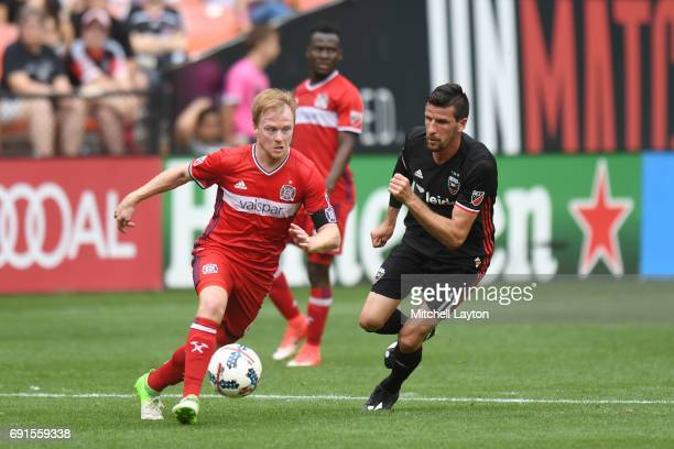 Dax McCarty of Chicago Fire dribbles by Sebastien Le Toux of DC United during a MLS Soccer game at RFK Stadium on May 20 2017 in Washington DC The...
