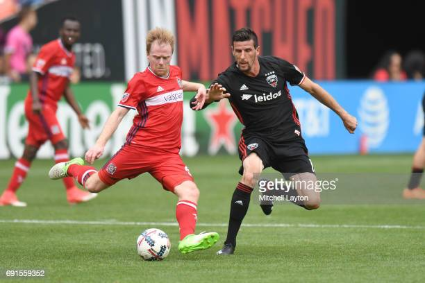 Dax McCarty of Chicago Fire takes shot by by Sebastien Le Toux of DC United during a MLS Soccer game at RFK Stadium on May 20 2017 in Washington DC...