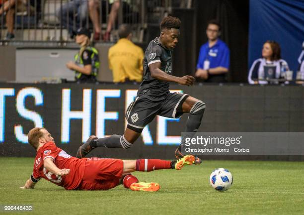 Dax McCarty of the Chicago Fire tries to slide tackle Alphonso Davies of the Vancouver Whitecaps FC at BC Place on July 7 2018 in Vancouver Canada