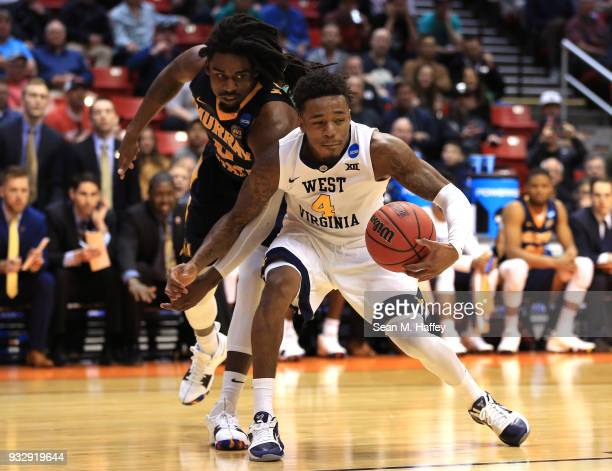 Daxter Miles Jr #4 of the West Virginia Mountaineers handles the ball against Terrell Miller Jr #0 of the Murray State Racers in the second half...