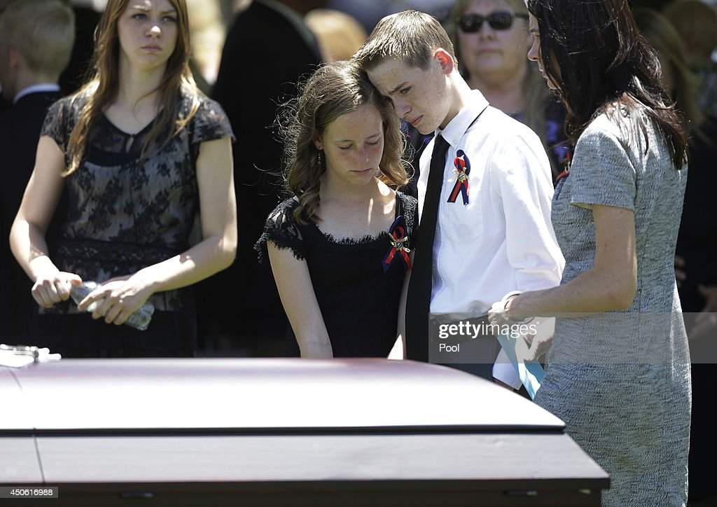 Daxton Beck, center right, leans his head on his sister Avenlee Beck as they stand over the casket of their father Las Vegas Metropolitan Police Officer Alyn Beck during a memorial at The Smith Center for the Performing Arts Saturday, on June 14, 2014 in Las Vegas, Nevada. Police said Beck and Officer Igor Soldo were shot and killed on June 8 at a restaurant by Jerad Miller and his wife Amanda Miller. Police said the Millers then went into a nearby Wal-Mart where Amanda Miller killed Joseph Wilcox before police killed Jerad Miller and Amanda Miller killed herself.