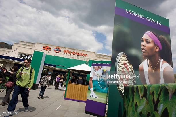 Day 2 of the annual lawn tennis championships and spectators mingle with locals near a large billboard of Ladies champion Serena Williams seen...