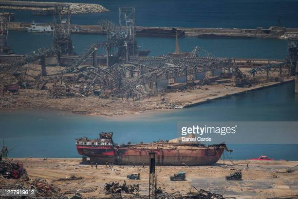 Day after a massive explosion occurred, people walk past a boat that received damages at the port on Aug. 5, 2020 in Beirut, Lebanon. As of Wednesday...