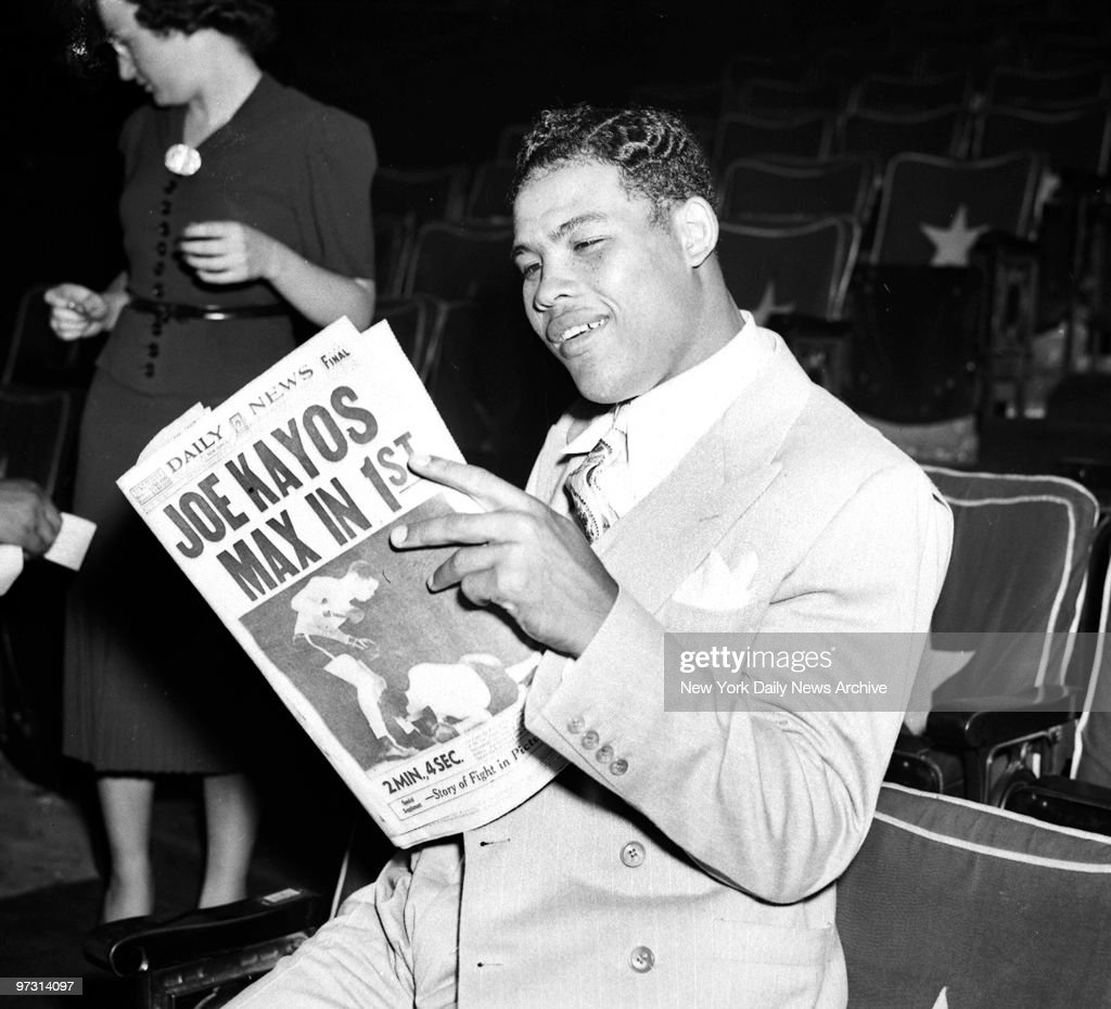Day after Joe Louis versus Max Schmeling II fight., The usually immobile countenance of the champ yields to a smile as Joe reads some highly interesting literature, copiously illustrated. He sees himself as others saw him.