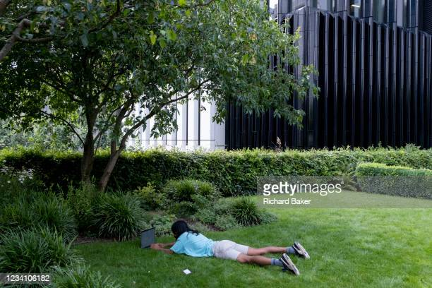 Day after the Covid 'Freedom Day', when social distancing and the wearing of face coverings are no longer mandatory, a man lies on the grass beneath...