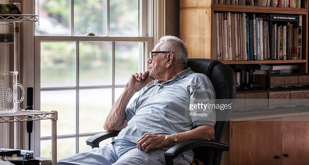 Day Dreaming Elderly Senior Man Staring Through Hazy Window : Stock Photo