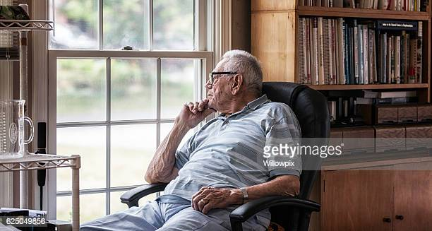 day dreaming elderly senior man staring through hazy window - warzen stock-fotos und bilder