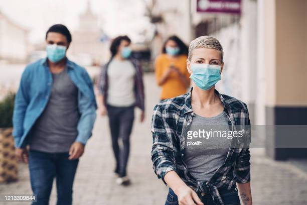 a day in the city during flu epidemic - protective face mask stock pictures, royalty-free photos & images