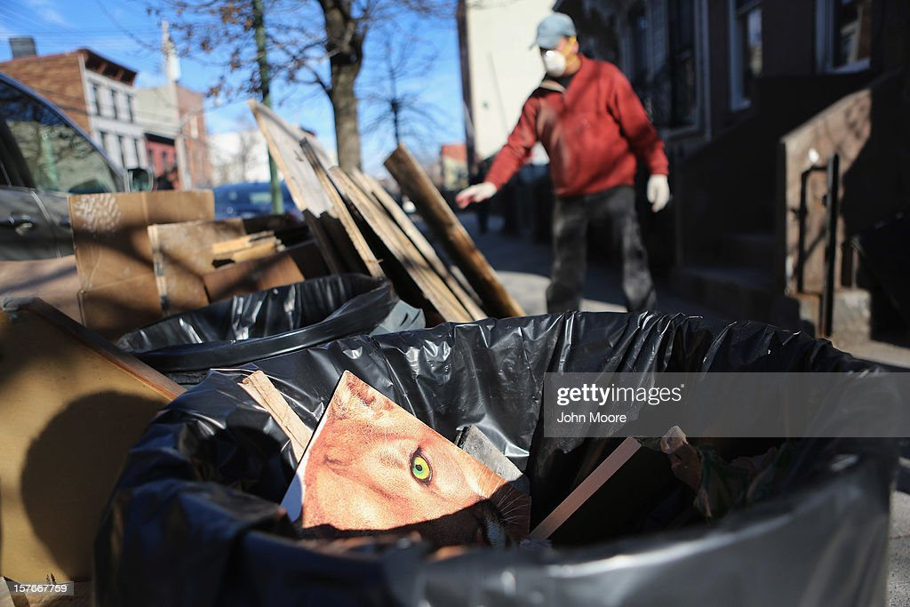 A day laborer removes debris from a flood-damaged home in the Red Hook neighborhood of Brooklyn on December 5, 2012 in New York City. More than a month after superstorm Sandy flooded the area, many homes remain vacant and businesses have been slow to reopen in the neighborhood.