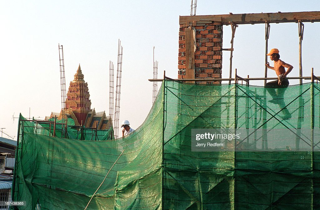 A day laborer works on a wall on a re-furbished guesthouse in Phnom Penh. The men on the construction site make on average the equivalent of $1 USD a day. Wat Ounalom, the center of Cambodian Buddhism, is visible in the background..