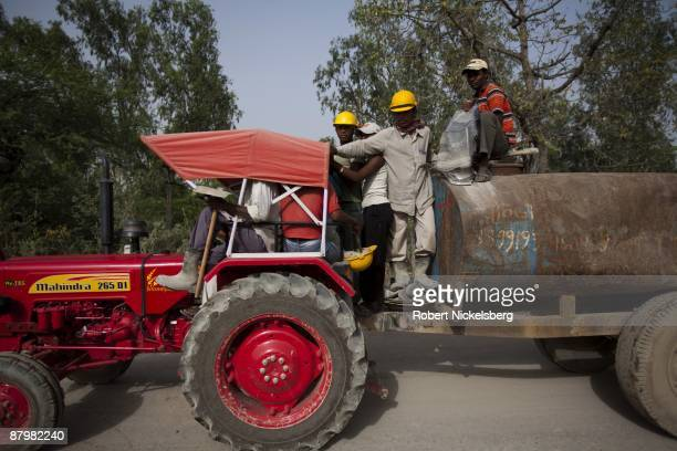 Day laborers are driven past a slum near a newly dug roadway April 21 2009 where agricultural land members of twelve families have been farming for...