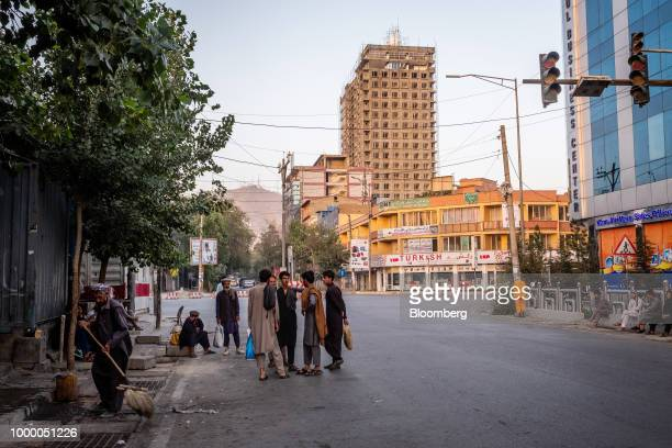 Day laborers stand waiting on the side of a road in Kabul Afghanistan on Sunday July 15 2018 A high rise building under construction in the...