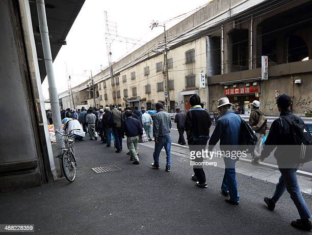 Day laborers wait in line to enter a shelter for homeless people in the Airin area of Nishinari ward in Osaka Japan on Friday May 2 2014 Osaka...