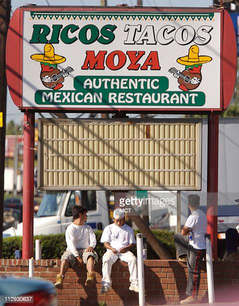 Day laborers wait under the sign of a Mexican restaurant in Woodbridge, Virginia, on September 12 waiting for employers looking to hire temporary...