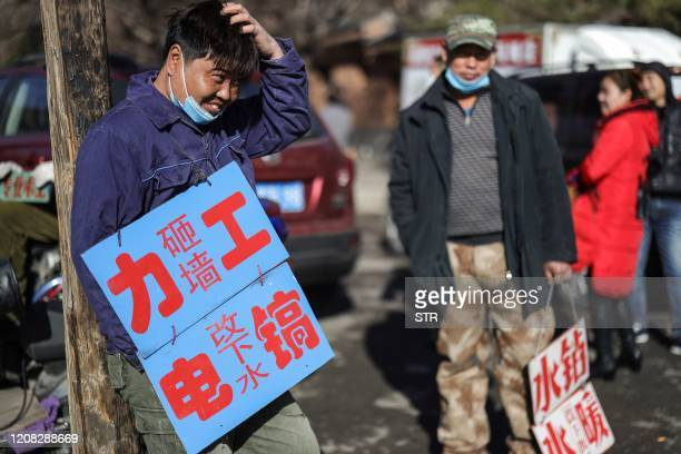 Day labourers wearing face masks hold signs advertising their skills as they wait to get hired for renovation works in Shenyang in China's...