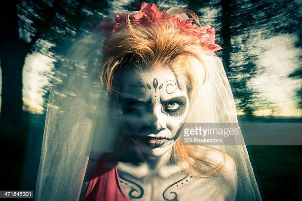 Day of the dead bride in elaborate costume and makeup