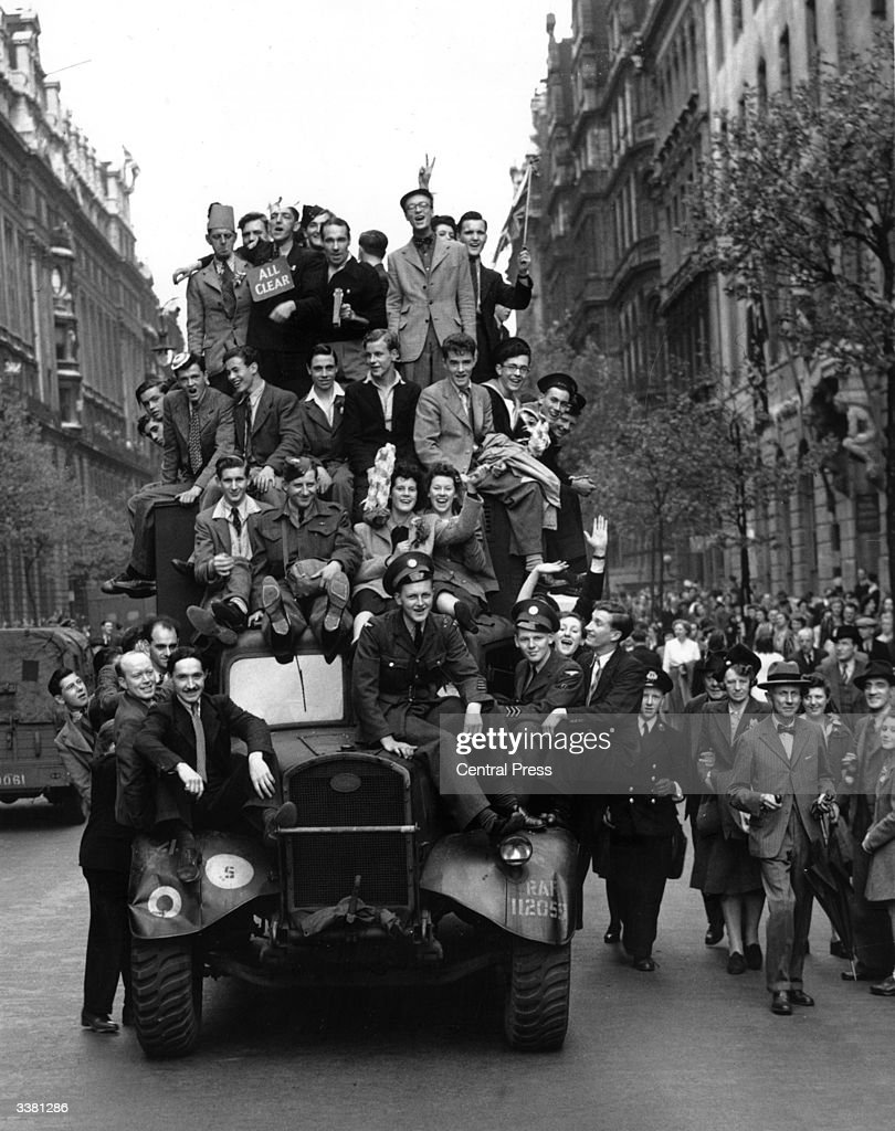 VE Day revellers hitching a ride on a lorry in London.