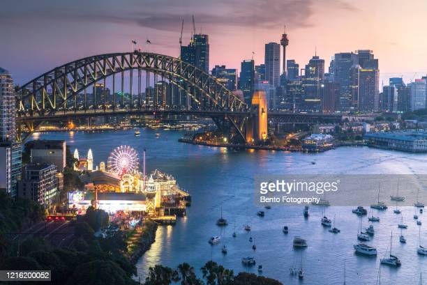 day to night luna park and harbour bridge in sunset from north sydney, sydney, australia - luna park sydney stock pictures, royalty-free photos & images
