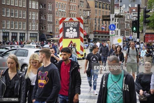 Day trippers and tourists walk in Amsterdam on July 25, 2020 as the municipality has stricter supervision over the weekend and one-way traffic was...