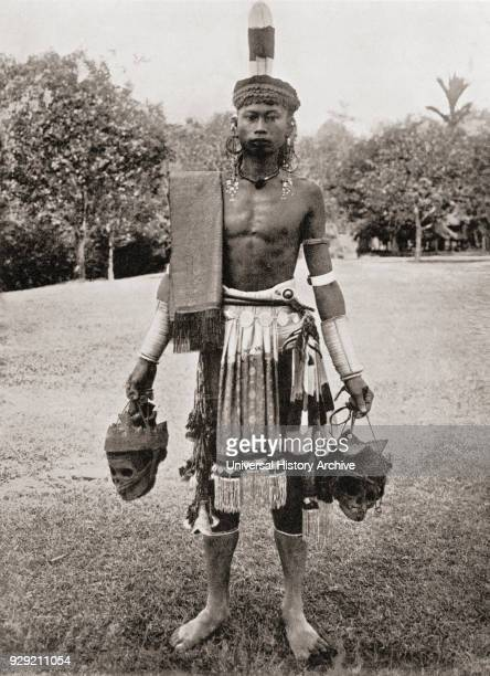 A Dayak Dyak or Dayuh man from the island of Borneo seen here in gala costume Every year or two the Dayaks hold a feast called Gawai Autu in honour...