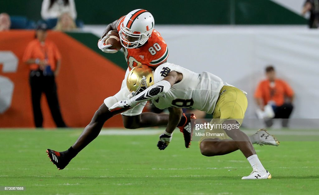 Dayall Harris #80 of the Miami Hurricanes is tackled by Donte Vaughn #8 of the Notre Dame Fighting Irish during a game at Hard Rock Stadium on November 11, 2017 in Miami Gardens, Florida.