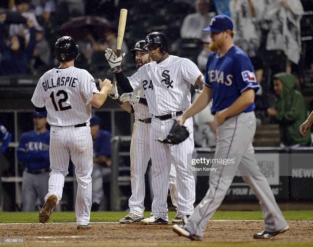 Dayan Viciedo #24 and Adam Eaton #1 of the Chicago White Sox (C) high-five teammate Conor Gillaspie #12 at home plate after Gillaspie and Viciedo scored on an RBI single hit by Tyler Flowers off of relief pitcher Nate Adcock #57 of the Texas Rangers (R) during the sixth inning at U.S. Cellular Field on August 4, 2014 in Chicago, Illinois.