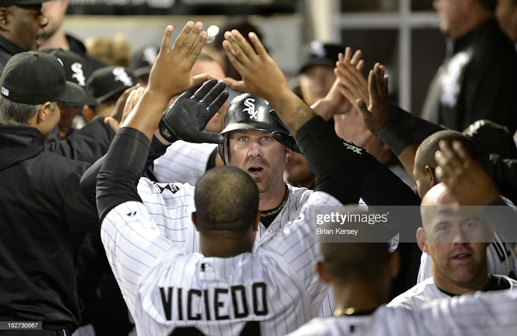 Dayan Viciedo #24 of the Chicago White Sox (L) high-fives teammate Adam Dunn #32 after Dunn hit a three-run home run during the eighth inning against the Cleveland Indians at U.S. Cellular Field on September 24, 2012 in Chicago, Illinois. The White Sox defeated the Indians 5-4.