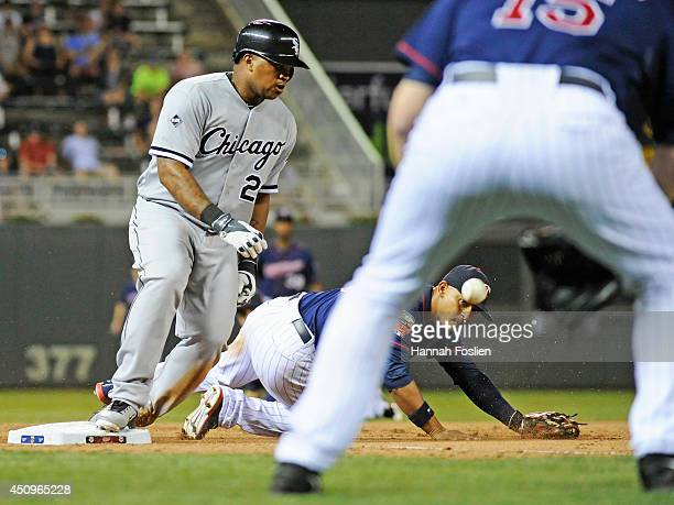 Dayan Viciedo of the Chicago White Sox slides into third base safely as Glen Perkins of the Minnesota Twins backs up teammate Eduardo Escobar as the...
