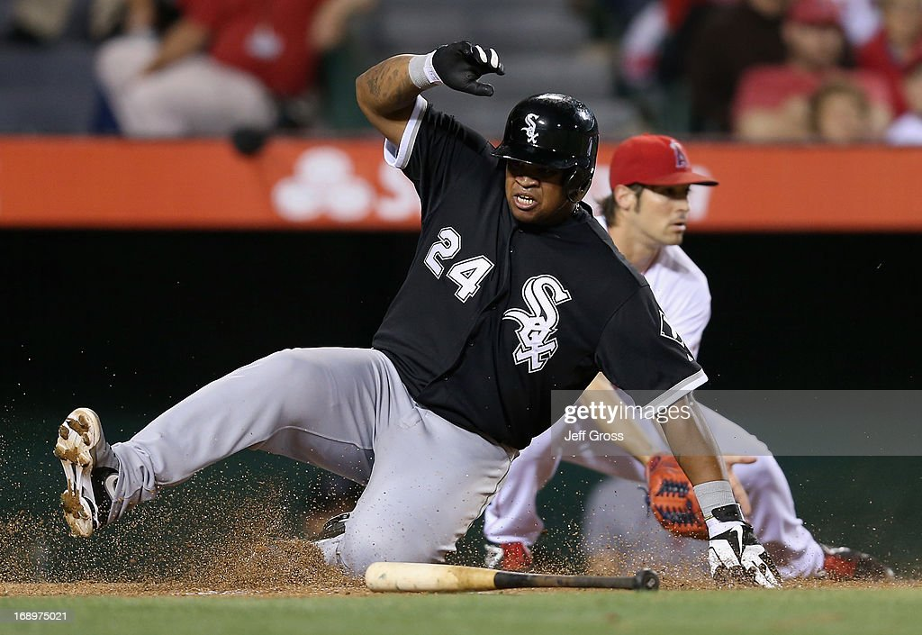 Dayan Viciedo #24 of the Chicago White Sox slides safely past pitcher C.J. Wilson #33 of the Los Angeles Angels of Anaheim and scores a run in the seventh inning at Angel Stadium of Anaheim on May 17, 2013 in Anaheim, California.
