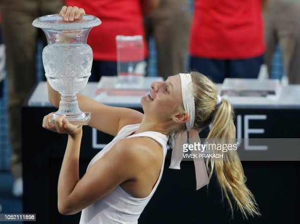 Dayana Yastremska of Ukraine poses with the champion's trophy after winning her women's singles final match against Wang Qiang of China at the Hong...