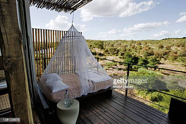 Daybed with mosquito net on game viewing deck of Savanna Private Game Lodge, South Africa.