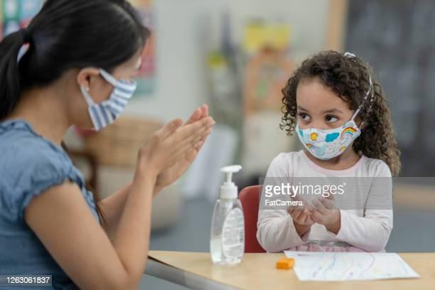 facilitador de creche fornece desinfetante para uma jovem usando uma máscara - criança de escola fundamental - fotografias e filmes do acervo