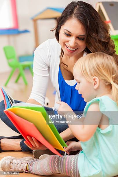 daycare teacher reading to cute toddler girl - baby pointing stock photos and pictures